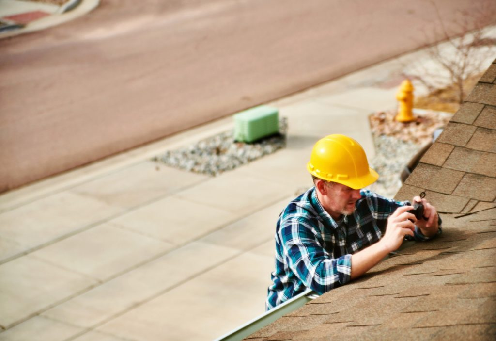 Home Appraiser or Home Inspector surveying roof of property