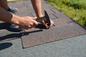Roofer installing Asphalt Shingles on a house construction roof corner with a hammer and nails. Roofing construction with Asphalt Shingles.