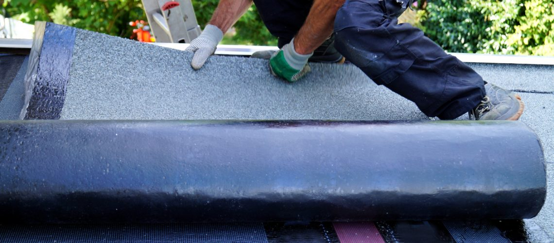 worker installing tar foil on the rooftop of building. Flat roof installation. Waterproof system by gas and fire torching.