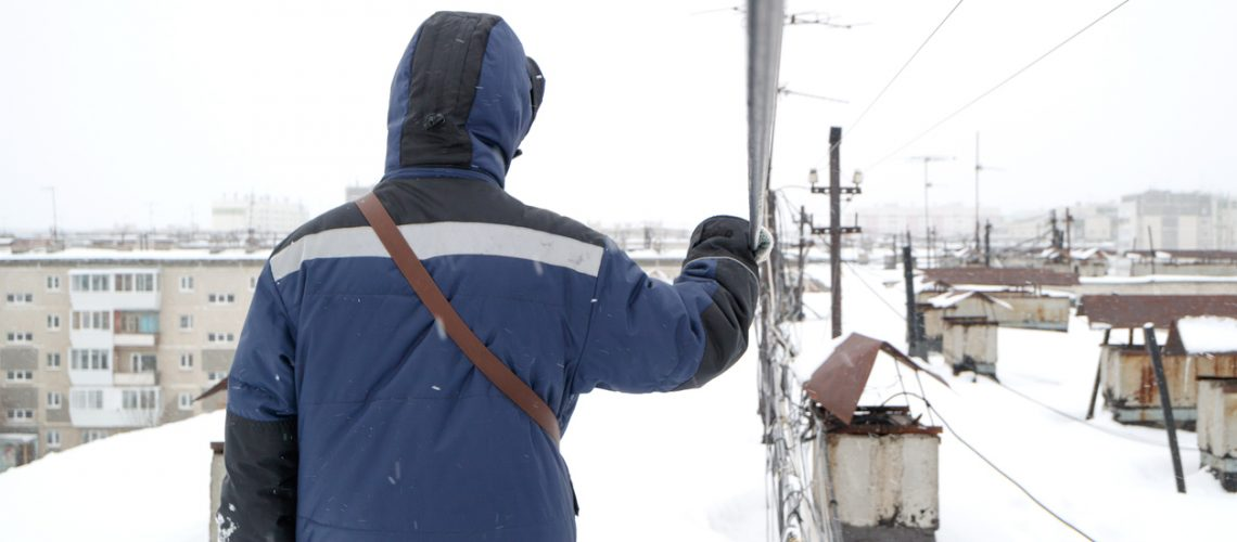 An employee working in the communications industry is looking for an optical link accident and holds his hand on the cable during a snowfall and extreme cold