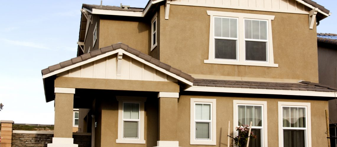 Brown stucco home with white trim against a blue sky