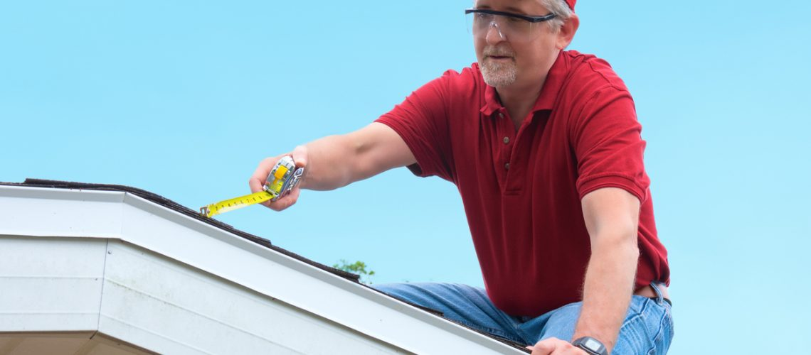 Wind mitigation inspection inspector wearing safety goggles doing inspection on new roof to generate a risk rating